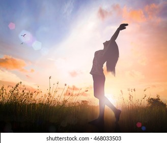World mental health day concept: Silhouette of healthy woman raised hands for praise and worship God at autumn sunset meadow background