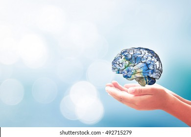 World mental health day concept: Human hands holding brain of earth over blurred blue nature background. Elements of this image furnished by NASA
