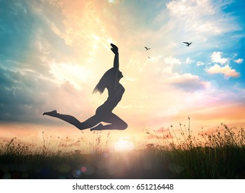 World mental health day concept: Silhouette of vital woman jumping at sunset meadow with her hands raised on amazing colorful sunset background