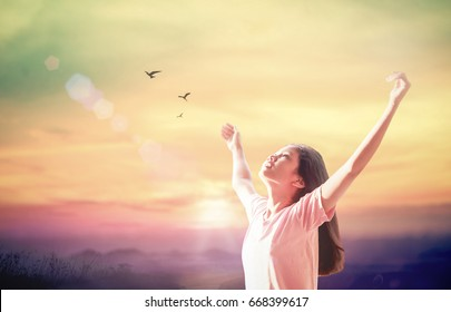 World mental health day concept: Beautiful woman raised up hand and opened arms for praise worship God on sunset background