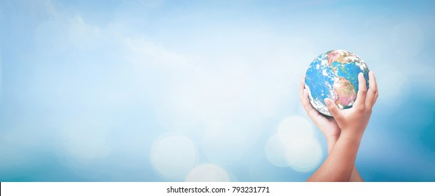 World mental health day concept: Two human hands holding earth globe over blurred blue water background. Elements of this image furnished by NASA
