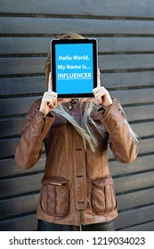 """Hello world, my name is influencer"" text on tablet in young blogger woman hands. Who are the influencers in your life?"