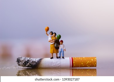 World no tobacco day. Cigarette and family figure. a concept for stop smoking. Smoking a cigarette can kill everyone in family. Save family from smoking. Smoke cigarettes hurt people in the family.