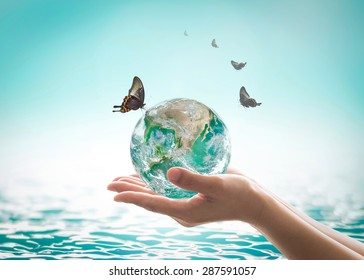 World ocean day, saving water, environmental protection, sustainable ecological ecosystems concept with green earth on woman's hands on sea background: Element of this image furnished by NASA