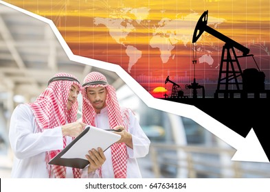 World oil industry falling prices concept . Two of arab businessman checking oil price on mobile and document chart with graph falling down background.