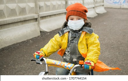 World pandemic corona virus. Covid 19. coronavirus pandemic. child wearing surgical mask. Active little boy in a protective mask on his face, rides a bicycle in a quarantine city.
