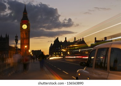 As the world passes by a taxi cab stops on Westminster Bridge next to the Houses of Parliament in London