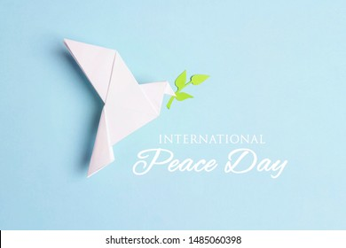 World Peace Day greeting card. Paper origami dove of peace with olive branch and text on a blue background.