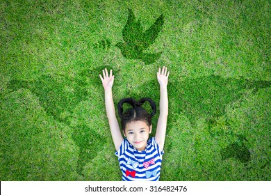 World peace day and International day of peace concept with peaceful mind kid resting in clean natural environment on eco friendly green lawn world map and dove