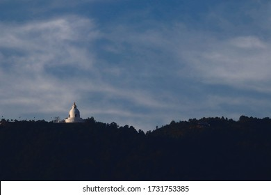 The world peace pagoda in Pokhara, Nepal, illuminated by the rising sun, with a cloudy blue sky in the background (off-center)