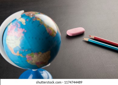 The world and pen-eraser on a chalkboard
