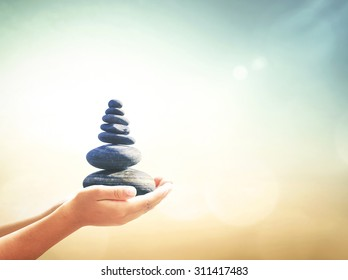 World philosophy day concept: Human hands holding balanced rocks over sunset beach background