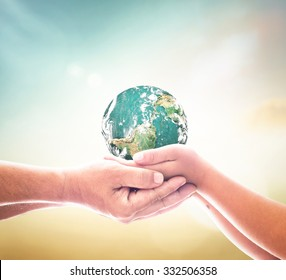 World population day concept: Two human hands holding earth global over blurred green nature background. Elements of this image furnished by NASA