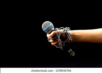 World press freedom day concept. Woman hand with microphone tied with a chain, depicting the idea of freedom of the press or freedom of expression on dark background.