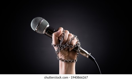 World press freedom day concept. Hand holding a microphone with chain on dark background, symbol of press freedom or speech freedom.