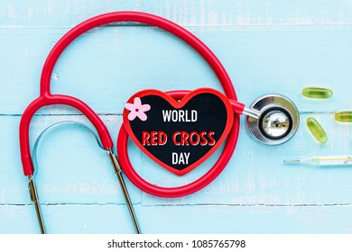 World Red Cross and Red Crescent day, May 8. Healthcare and medical concept. Stethoscope, red and black heart, thermometer and yellow Pill on Pastel white and blue wooden table background texture.