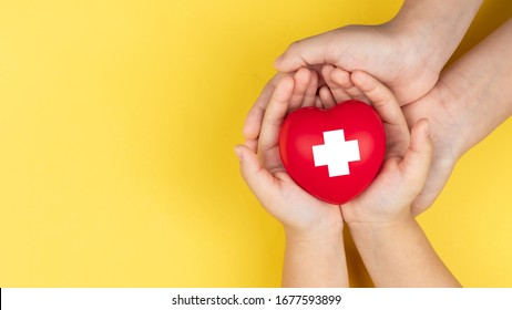 world red cross day, adult and child hands holding red heart, healthcare, love and family insurance concept
