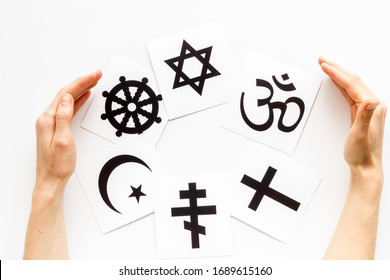 World religions concept. Hands hugs Christianity, Catholicism, Buddhism, Judaism, Islam symbols on white background top view