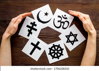 World religions concept. Hands hugs Christianity, Catholicism, Buddhism, Judaism, Islam symbols on wooden background top view - Shutterstock ID 1706328310