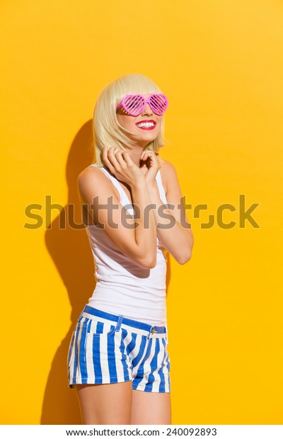 World through rose colored glasses. Beautiful blond girl in pink sunglasses smiling. Three quarter length studio shot on yellow background.
