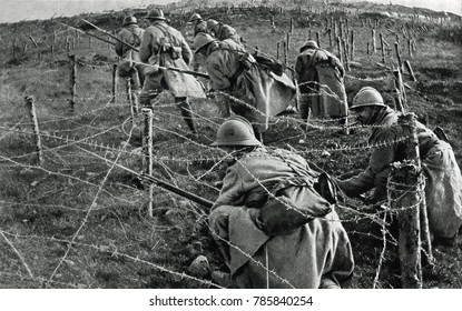 World War 1: Battle of Verdun. French soldiers crawling through their own barbed wire entanglements as they begin an attack on enemy trenches. April-June, 1916.