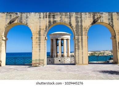 World War II Siege Bell War Memorial through archs in the Lower Barrakka Gardens, Valletta, Malta