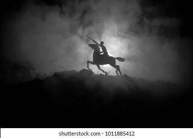 World war officer (or warrior) rider on horse with a sword ready to fight and soldiers on a dark foggy toned background. Battle scene battlefield of fighting soldiers. Selective focus