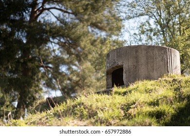 A World War Two concrete pillbox on the hill in Russia near the Moscow. Shows the entrance, an embrasure and a central anti aircraft gun well on top. Background of trees