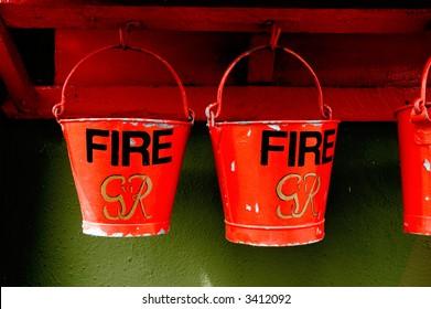 World war two vintage fire buckets on green wall