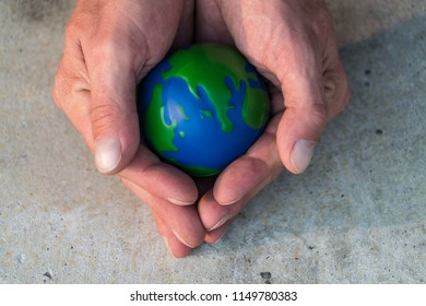 World is in your hands. man holds small planet earth sphere in the palms of his hands and protects our environment for future generations