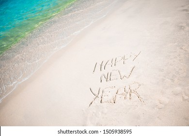 Worlds happy new year written in the sand of a beach