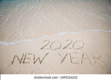 Worlds new year 2020 written in the sand of a beach