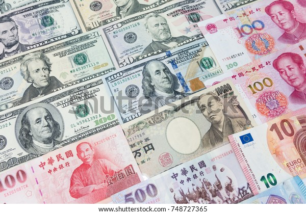 World's various currencies from several different countries. Closeup assorted American dollar bills and Asian currencies such as Chinese yuan, Taiwan dollar, Japanese yen and Euro used for background.