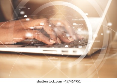 Worldwide connection interface. Double exposure of African American businesswoman typing a message via e-mail using laptop while sitting at the wooden table in the office. Selective focus on hands