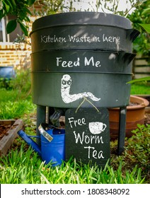 Worm farm, wormery, compost bin in organic garden with sign for Free Worm Tea, feed me and kitchen waste in here, sustainable living and zero waste lifestyle