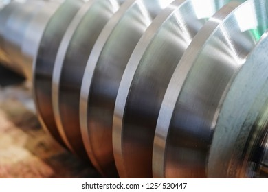 The worm shaft after machining lies on a wooden rack and is ready for use in mechanical engineering and metallurgy. Photo threaded coils close-up.