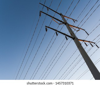 Worm's eye view of power lines against a blue sky with orange highlights.