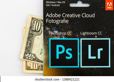 WORMS / GERMANY - MAY 04, 2019: A voucher of a photography plan with two 10 dollar bills behind it. Adobe is testing price changes to their popular plan and removed the 10 dollar option for some users