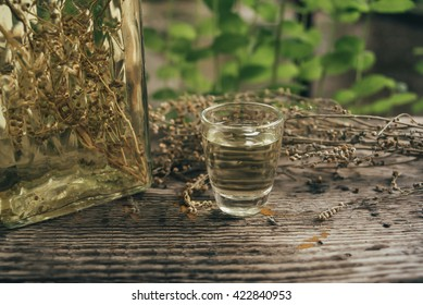 Wormwood drinks in a small glass on rustic board