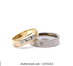 Worn and battered mens rings in gold and titanium against white background.
