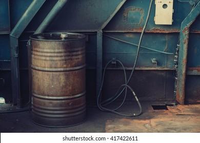 Worn black metal barrel with fuel oil. Industrial background.