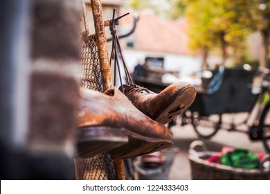 Worn brown leather shoes with holes in the soles, hanging on old vintage fence with the laces tied
