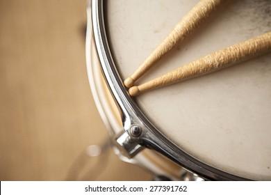 Worn drum sticks on top of a snare drum.
