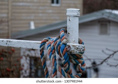 A worn fishing rope, red, blue and white in color, wrapped around a white metal fence post. There's a white building in the background.