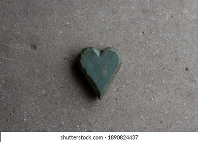 Worn green wooden heart on concrete surface