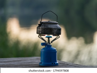 Worn kettle on cooking equipment. Hiking gear used on trekking. Aluminium tea pot on camping gas accessory. Steam coming out. Warm summer evening in Finland by river Kymi.