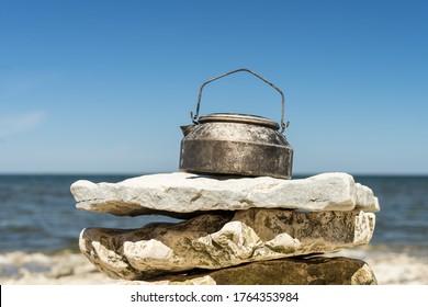 Worn kettle on limestone rock on seashore. Hiking gear put aside. Cooking accessory used on trekking. Aluminium tea pot on rocks. Sunny warm summer day, blue sky calm sea. Tiny islet in Estonia.