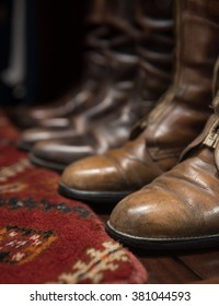 Worn Leather Boots with Patterned Carpet - Shutterstock ID 381044593