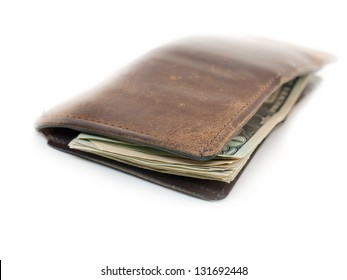 A worn leather wallet with U.S. dollars.
