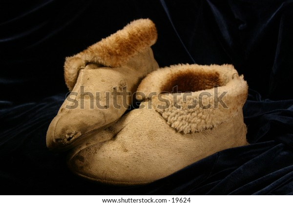 Worn moccasins on dark background symbolize diversity and the concept of understanding differences among staff.  Walk a mile in my shoes...